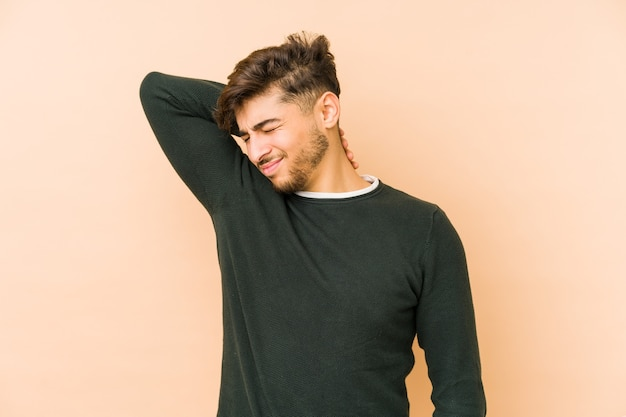 Young arabian man isolated on a beige background suffering neck pain due to sedentary lifestyle.