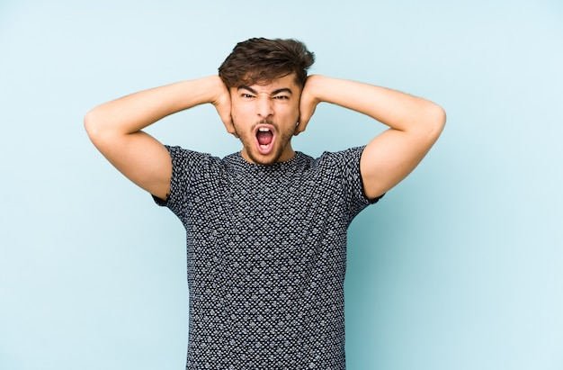 Young arabian man isolated on a blue background covering ears with hands trying not to hear too loud sound.