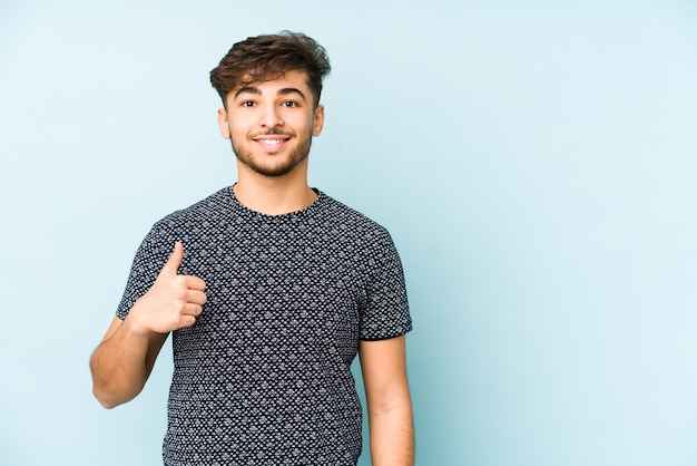 Young arabian man isolated on a blue background smiling and raising thumb up
