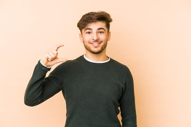 Молодой арабский мужчина изолирован на бежевой стене, держа что-то маленьким указательными пальцами, улыбаясь и уверенно.