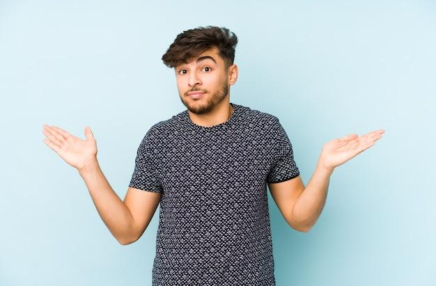 Молодой арабский мужчина изолирован на синей стене, сомневаясь и пожимая плечами в вопросительном жесте.