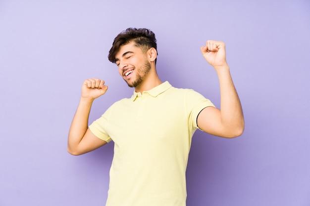 特別な日を祝う紫色の背景に孤立した若いアラビア人は、ジャンプしてエネルギーで腕を上げます。
