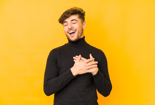 若いアラビア人は心、幸福の概念に手をつないで笑っている黄色の壁に分離されました。