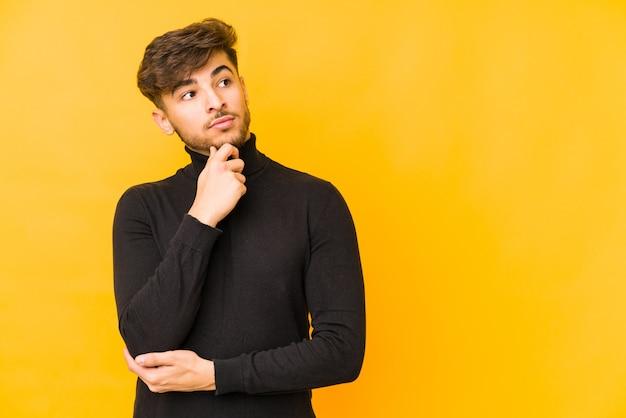 Молодой арабский мужчина изолирован на желтой стене, глядя в сторону с сомнительным и скептическим выражением лица.