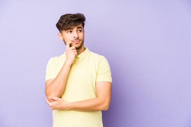 Молодой арабский мужчина изолирован на фиолетовом, глядя в сторону с сомнительным и скептическим выражением лица.