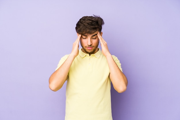 Young arabian man isolated on a purple wall touching temples and having headache.