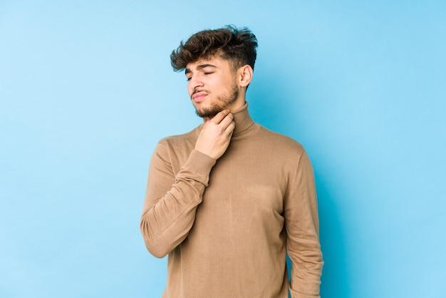 Изолированный молодой арабский мужчина страдает от боли в горле из-за вируса или инфекции.