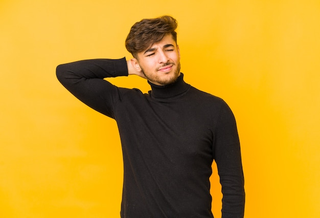 Young arabian man isolated on a yellow background suffering neck pain due to sedentary lifestyle.