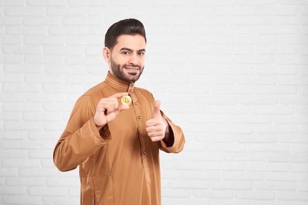 Young arabian man keeps bitcoin