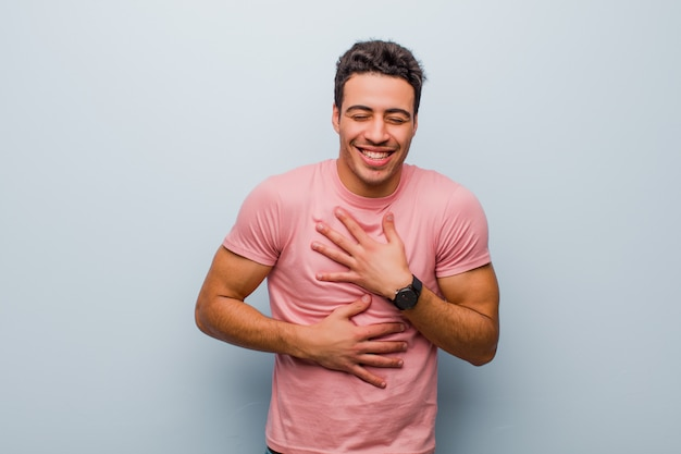 Young arabian man laughing out loud at some hilarious joke, feeling happy and cheerful, having fun on gray wall
