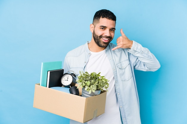 Young arabian man moving to a new home isolated showing a mobile phone call gesture with fingers.