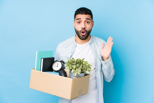 Young arabian man moving to a new home isolated surprised and shocked.