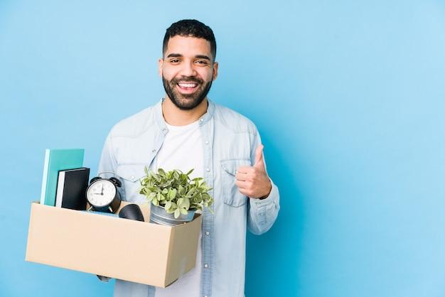 Молодой арабский мужчина, переезжающий в новый дом, изолированно улыбается и поднимает палец вверх