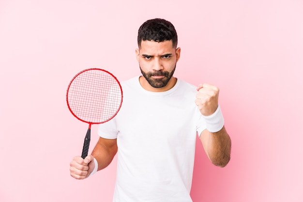 Молодой арабский человек, играя в бадминтон, изолировал, показывая кулак, агрессивное выражение лица.