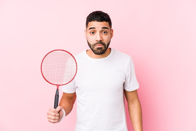 Young arabian man playing badminton isolated shrugs shoulders and open eyes confused.