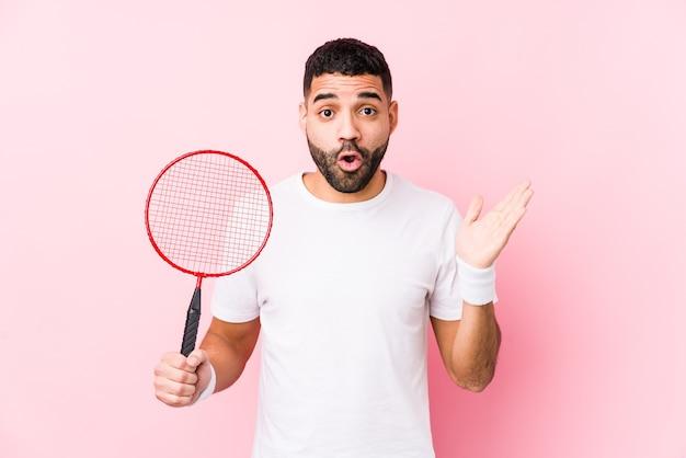 Молодой арабский человек, играя в бадминтон изолировал удивлен и шокирован.