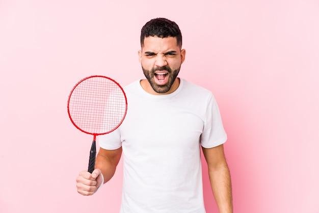 Молодой арабский человек играет в бадминтон, кричит очень злой и агрессивный.
