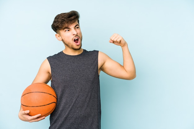 Young arabian man playing basket isolated raising fist after a victory, winner concept.