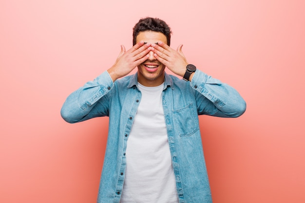 Young arabian man smiling and feeling happy, covering eyes with both hands and waiting for unbelievable surprise against pink wall