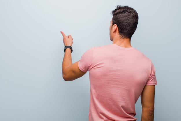 Young arabian man standing and pointing to object on copy space, rear view against gray wall