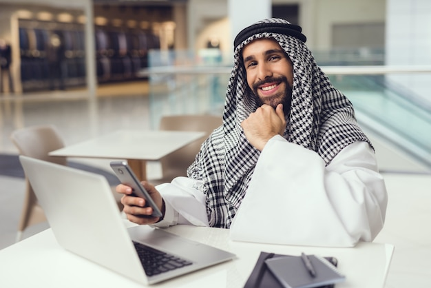 Young arabian man using phone and laptop in cafe
