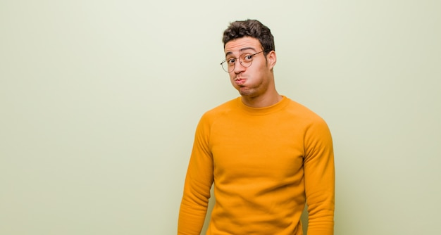 Young arabian man with a goofy, crazy, surprised expression, puffing cheeks, feeling stuffed, fat and full of food against flat wall