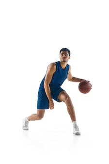 Young arabian muscular basketball player in action, motion isolated on white