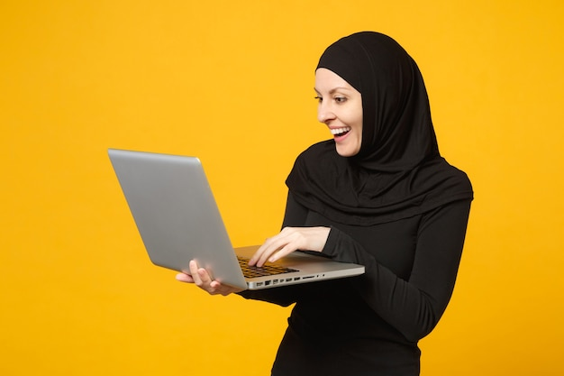 Young arabian muslim employee woman in hijab black clothes hold and work laptop pc computer isolated on yellow wall  portrait. people religious lifestyle concept.