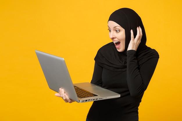 Молодой арабский мусульманский служащий женщина в черной одежде хиджаба держит и работает портативный компьютер, изолированный на желтой стене портрет. концепция религиозного образа жизни людей.