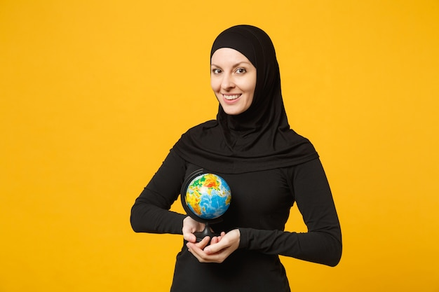 Young arabian muslim student girl in hijab black clothes hold in hands earth world globe isolated on yellow wall  portrait. people religious lifestyle concept.