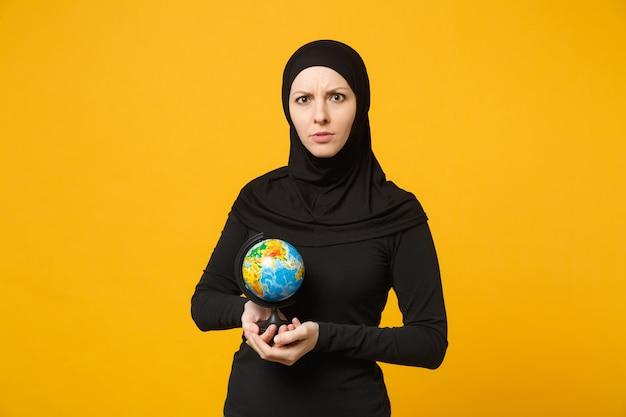 Молодая арабская мусульманская девушка студента в черной одежде хиджаба держит в руках глобус мира земли изолированный на портрете желтой стены. концепция религиозного образа жизни людей.