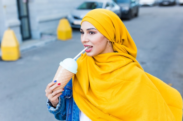 Young arabian muslim woman enjoying cocktail outdoor.