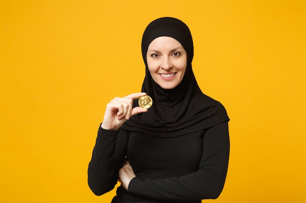 Young arabian muslim woman in hijab black clothes hold in hand holding bitcoin coin currency isolated on yellow wall  portrait. people religious lifestyle concept.
