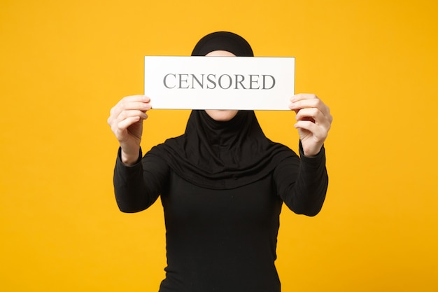 Young arabian muslim woman in hijab black clothes hold in hands sign with censored title isolated on yellow wall  portrait. people religious lifestyle concept. .