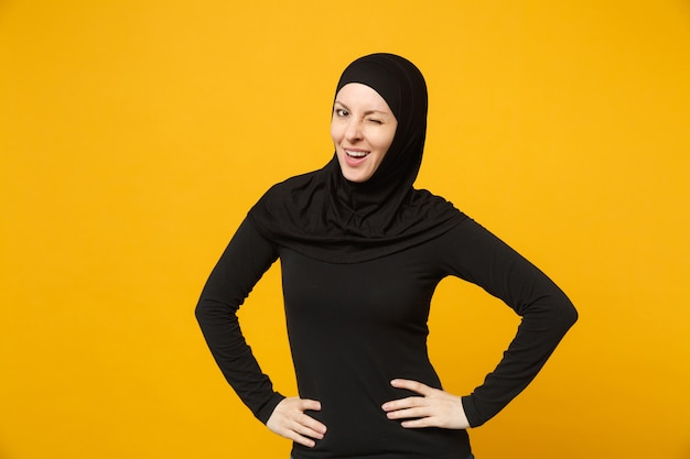 Young arabian muslim woman in hijab black clothes standing with arms akimbo on waist isolated on yellow wall, portrait. people religious islam lifestyle concept.
