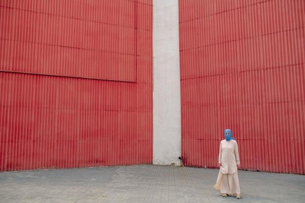 カジュアルな服装と赤い壁の都市環境でヒジャーブ立っている若いアラビアのイスラム教徒の女性