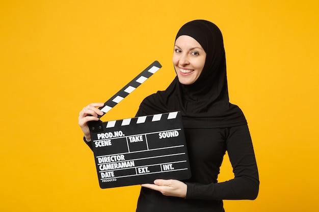 Молодая арабская мусульманка в черной одежде хиджаба держит классический черный фильм, делая с 'хлопушкой', изолированную на портрете на желтой стене. концепция религиозного образа жизни людей.