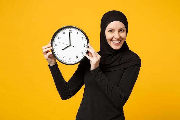 Hijab 검은 옷에 젊은 아라비아 무슬림 여성이 노란색 벽 초상화에 고립 된 라운드 시계 손에 개최. 사람들의 종교적 생활, 시간 관리 개념.