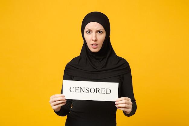 Hijab 검은 옷에 젊은 아라비아 무슬림 여성이 노란색 벽 초상화에 고립 된 검열 된 제목으로 손 기호에 개최. 사람들이 종교적인 라이프 스타일 개념. .