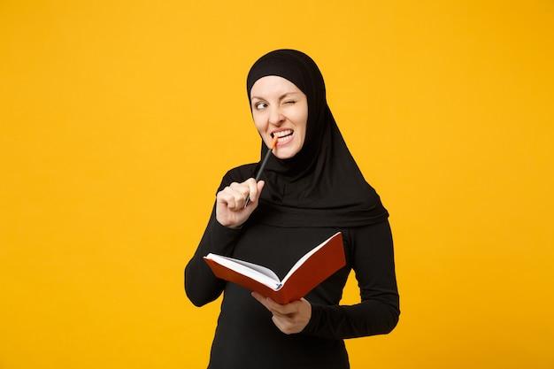 Hijab 검은 옷에 젊은 아라비아 이슬람 여자 잡고 노트북, 쓰기, 노란색 벽 초상화에 고립 된 시험 준비. 사람들이 종교적인 라이프 스타일 개념. .