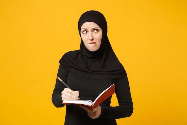 ヒジャーブの黒い服を着た若いアラビアのイスラム教徒の女性は、ノートを保持し、書き込み、黄色の壁の肖像画に分離された試験の準備をします。人々の宗教的なライフスタイルの概念。 。