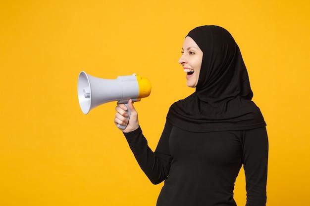 ヒジャーブの黒い服を着た若いアラビアのイスラム教徒の女性は、黄色の壁の肖像画に分離された拡声器のパブリックアドレスメガホンを手に持っています。人々の宗教的なライフスタイルの概念。