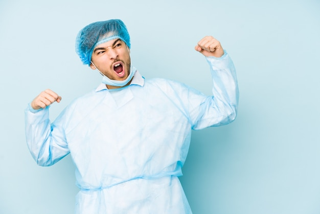 Young arabian surgeon man isolated against on a blue wall raising fist after a victory, winner concept.