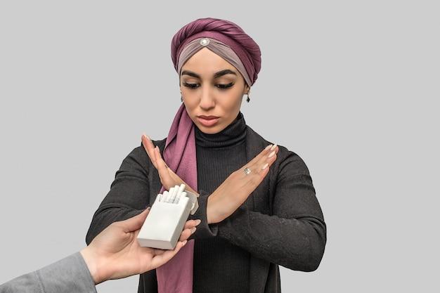 若いアラビアの女性は小さな箱でタバコに一時停止の標識を示しています。