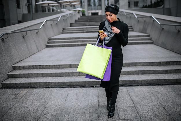 젊은 아라비아 여자 산책과 전화를 봐.