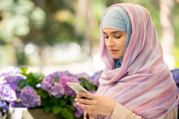 Young arabian woman wearing hijab scrolling in her smartphone while chilling out in park