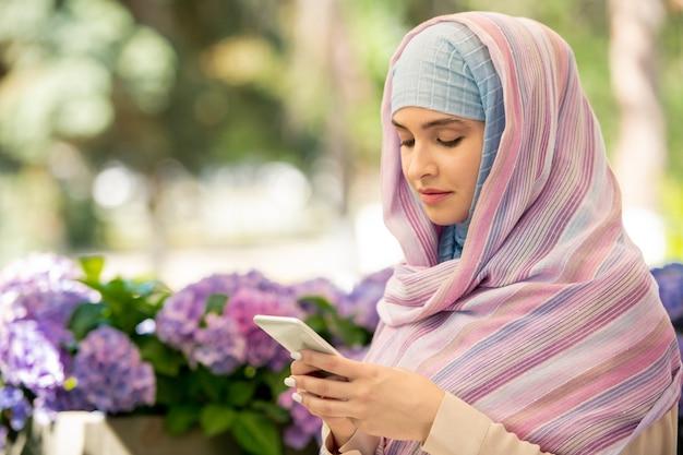 公園でリラックスしながら彼女のスマートフォンでスクロールヒジャーブを着ている若いアラビア女性