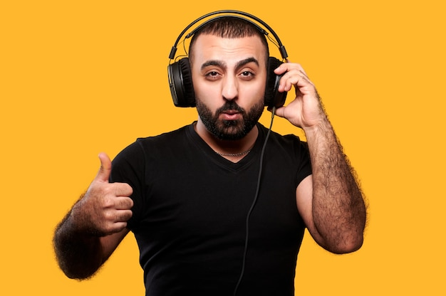헤드폰에서 음악을 듣고 엄지 손가락을 노란색으로 보여주는 수염을 가진 젊은 아랍 dj