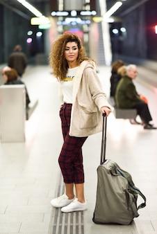 地下鉄の駅で彼女の列車を待っている若いアラビア語の女性観光客。