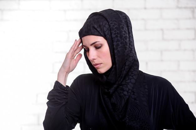 伝統的なアラビアのドレスを着た若いアラビアの女性は、屋内でポーズをとります。